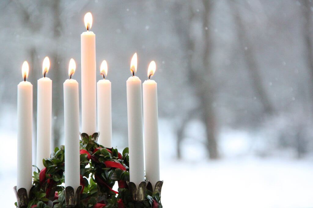 A wreath of lit candles burns in a snowy landscape