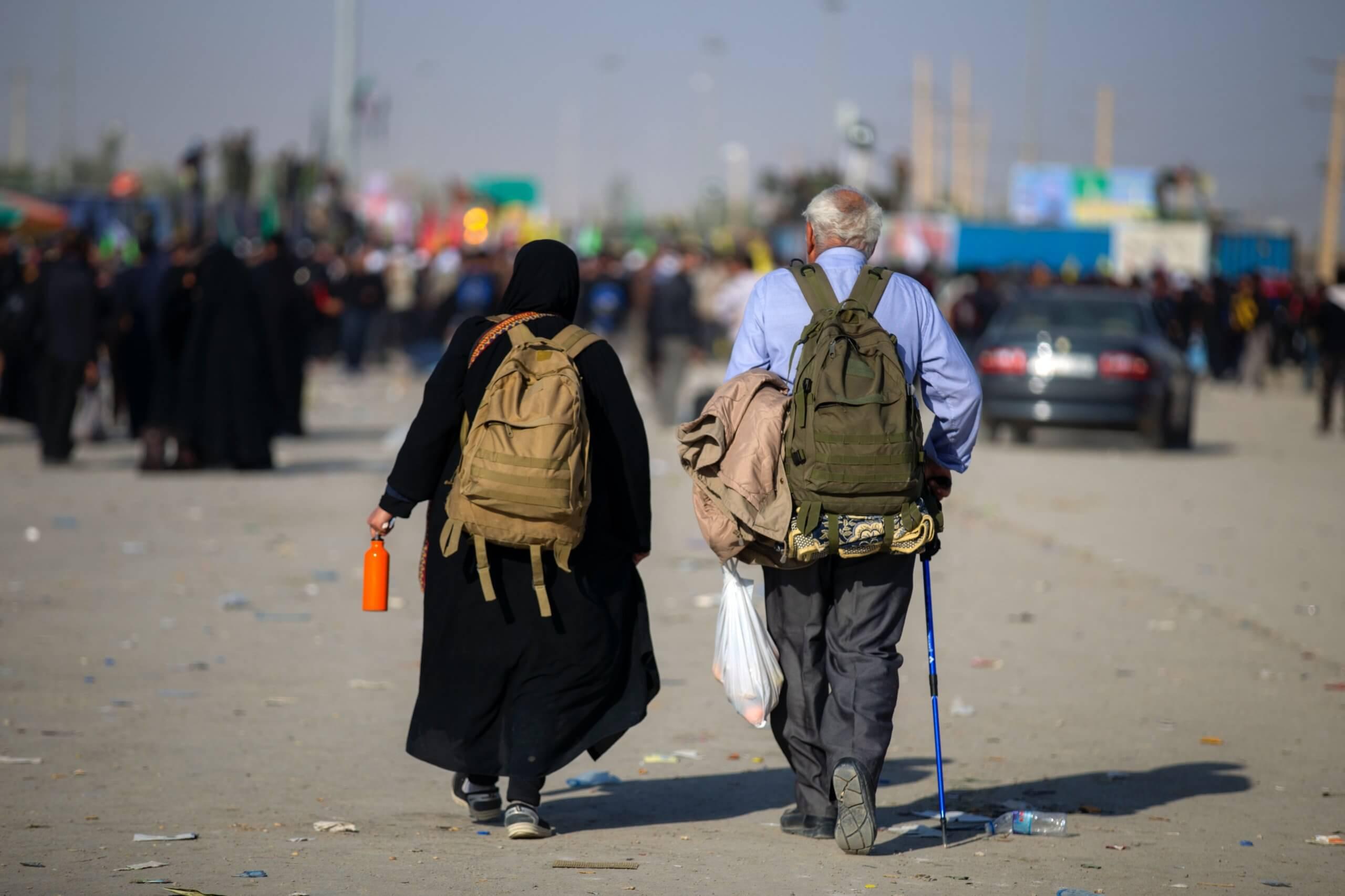 Two older people walk away from the camera. Photo by mostafa meraji on Unsplash